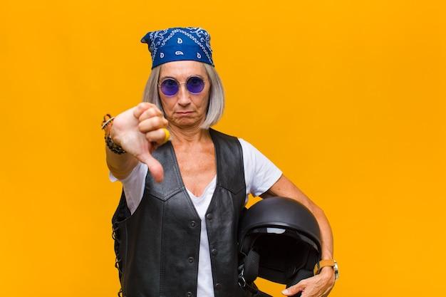 Mulher de meia-idade se sentindo zangada, irritada, irritada, decepcionada ou descontente, mostrando o polegar para baixo com um olhar sério
