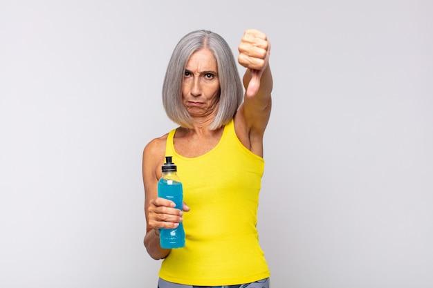Mulher de meia-idade se sentindo zangada, irritada, irritada, decepcionada ou descontente, mostrando os polegares para baixo com um olhar sério. conceito de fitness