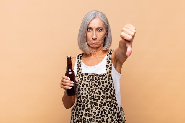 Mulher de meia-idade se sentindo zangada, irritada, irritada, decepcionada ou insatisfeita, mostrando o polegar para baixo com um olhar sério com uma cerveja