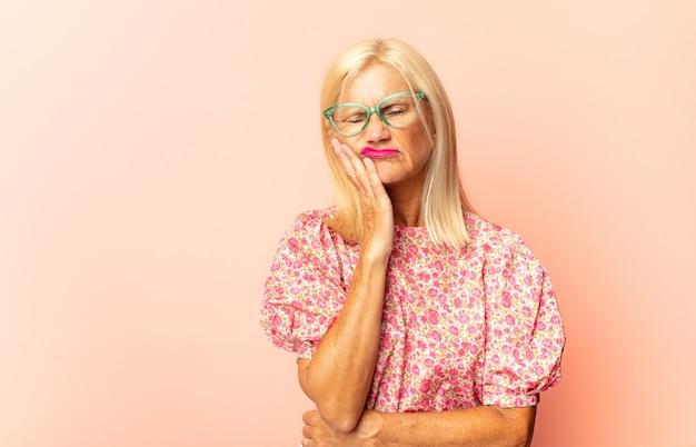 Mulher de meia-idade segurando a bochecha e sofrendo de dor de dente dolorida, sentindo-se doente, infeliz e infeliz, procurando um dentista