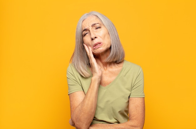 Mulher de meia-idade segurando a bochecha e sofrendo de dores de dente doloridas, sentindo-se doente, infeliz e infeliz, procurando um dentista