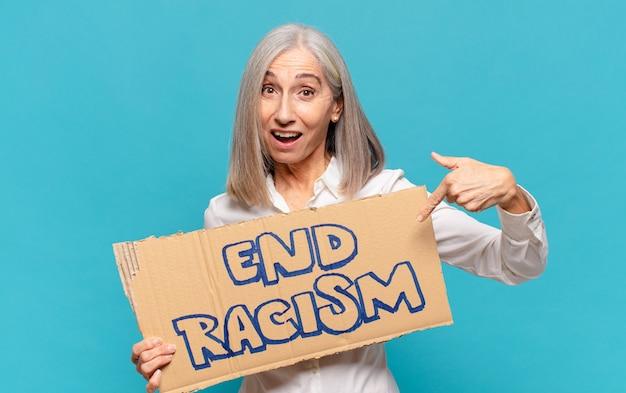 Mulher de meia-idade segurando placa de racismo