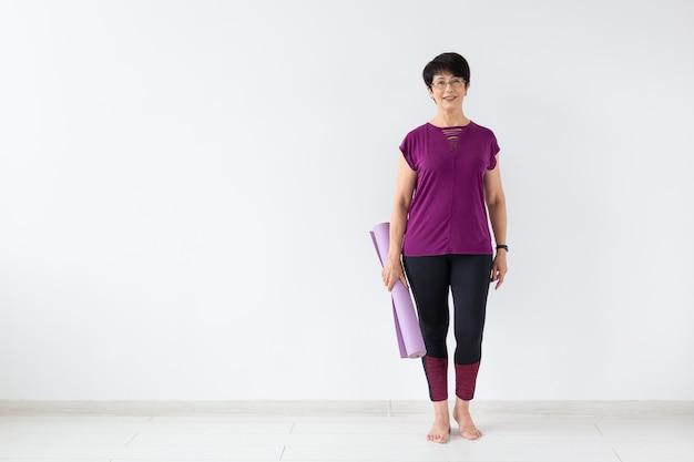 Mulher de meia-idade segurando tapete depois de uma aula de ioga