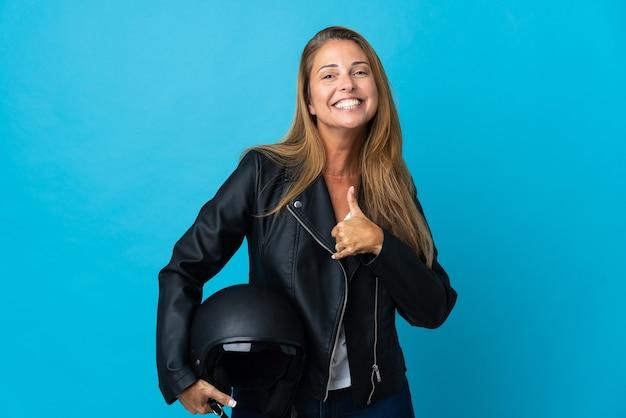 Mulher de meia-idade segurando um capacete de motociclista isolado e fazendo um gesto de polegar para cima