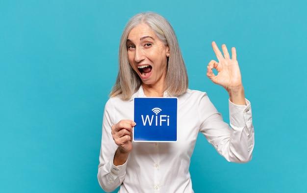 Mulher de meia-idade segurando um cartaz de wi-fi