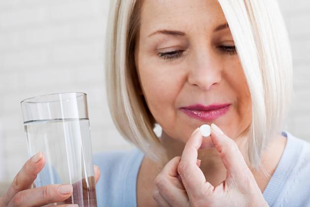 Mulher de meia-idade segurando um comprimido e um copo d'água