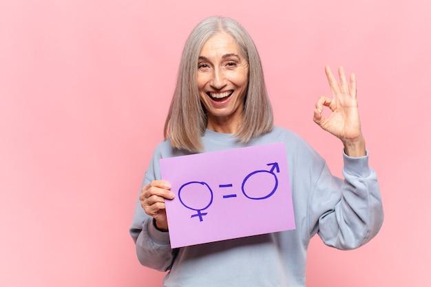 Mulher de meia-idade segurando um quadro de igualdade de gênero