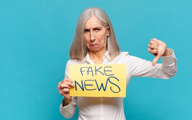 Mulher de meia-idade segurando um quadro de notícias falsas e apontando para baixo