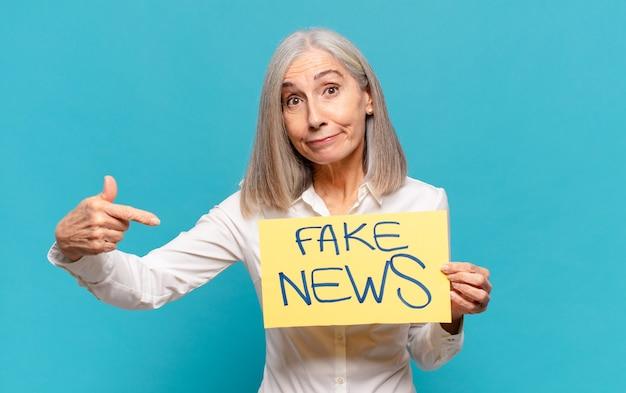 Mulher de meia-idade segurando um quadro de notícias falsas