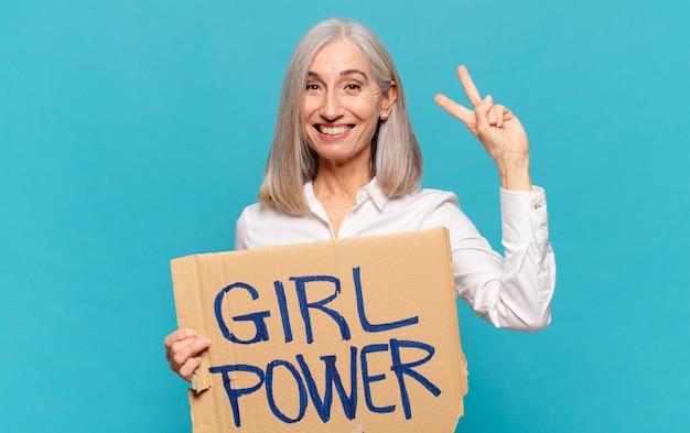 Mulher de meia-idade segurando uma placa com o texto girl power