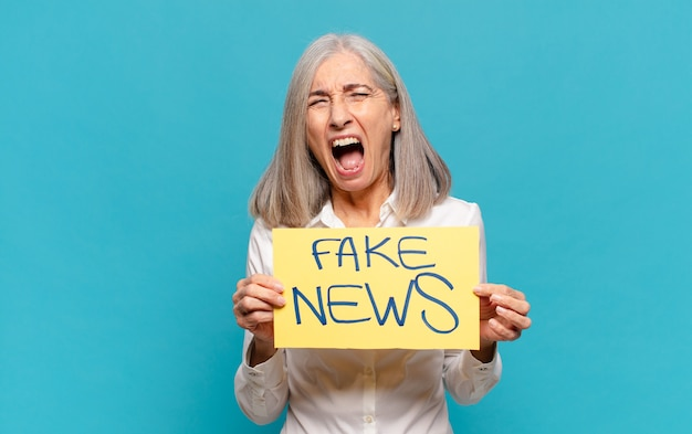 Mulher de meia-idade segurando uma placa com o texto notícias falsas
