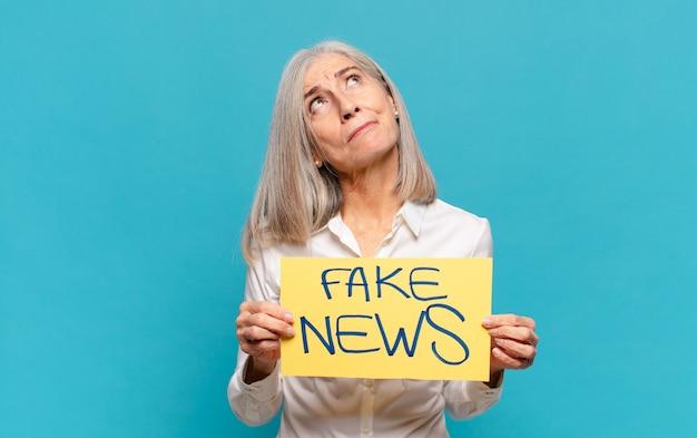 Mulher de meia-idade segurando uma placa de notícias falsas