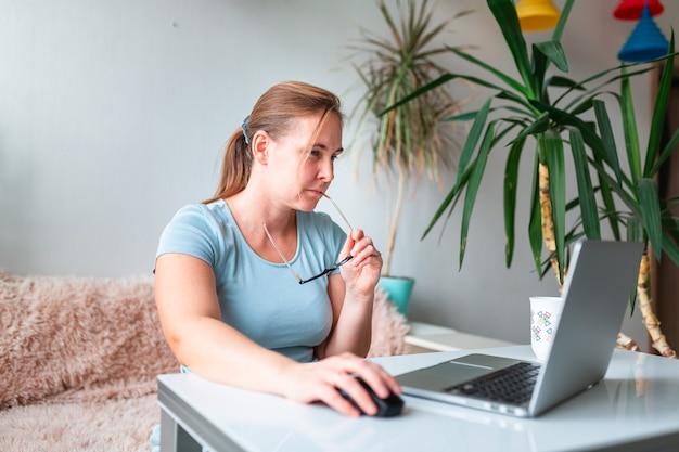 Mulher de meia-idade sentada à mesa em casa trabalhando usando o computador portátil. trabalhe em casa e fique em casa durante o conceito de pandemia de coronovírus