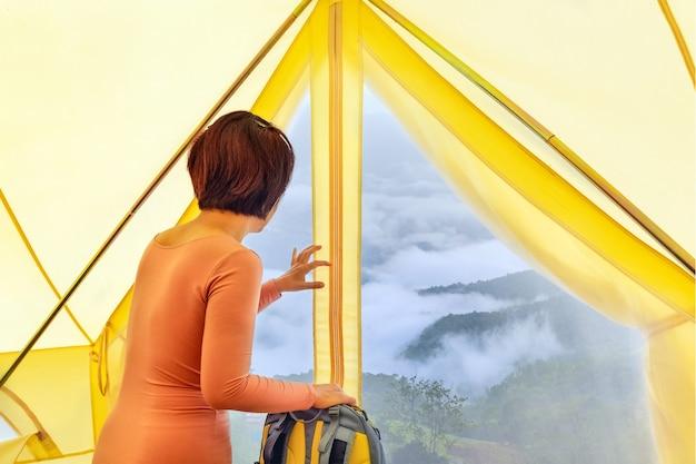 Mulher de meia-idade sentada dentro de uma tenda amarela olhando para o vale