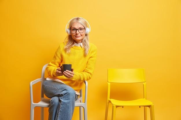 Mulher de meia-idade sentada em uma cadeira confortável, usando óculos transparentes, segurando uma caneca de café, ouvindo música com fones de ouvido