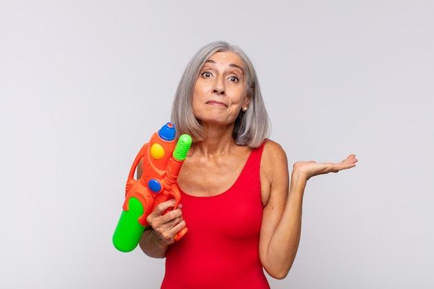 Mulher de meia idade sentindo-se perplexa e confusa, duvidando, ponderando ou escolhendo diferentes opções com expressão engraçada com uma pistola d'água