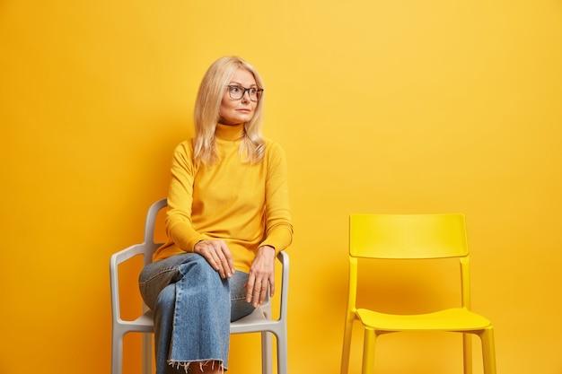 Mulher de meia-idade solitária sentada perto de uma cadeira vazia, precisa de comunicação, parece pensativa, vestida com uma blusa casual de gola alta e jeans