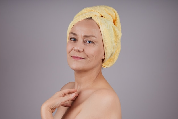Mulher de meia idade sorridente com ombros nus, aplicando creme na pele, de perfil na parede cinza. conceito de cuidado de pele facial.