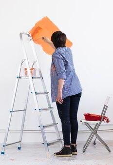 Mulher de meia-idade sorridente, pintando a parede interior da casa. renovação, reparo e redecoração