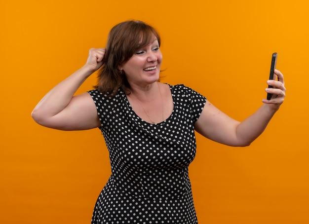 Mulher de meia-idade sorridente segurando um telefone celular e colocando o punho atrás da cabeça em uma parede laranja isolada
