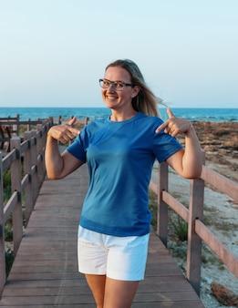 Mulher de meia idade sorridente usando óculos e t-shirt azul em pé na ponte de madeira à beira-mar ao pôr do sol. mulher apontando para a camiseta. maquete de camiseta