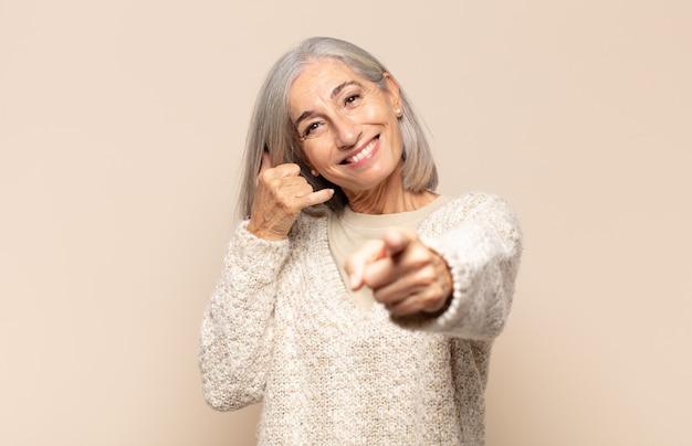 Mulher de meia-idade sorrindo alegremente e apontando para a câmera enquanto faz um gesto depois de ligar para você, falando ao telefone