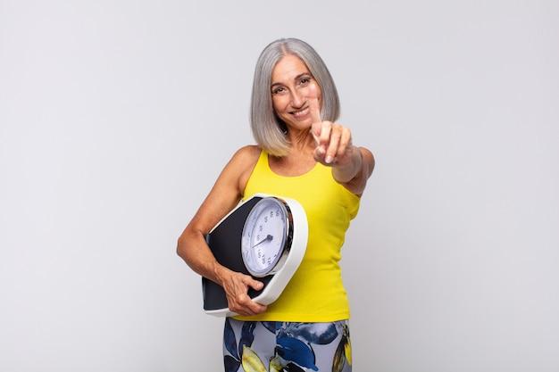 Mulher de meia-idade sorrindo com orgulho e confiança, fazendo a pose número um triunfantemente, sentindo-se uma líder. conceito de fitness