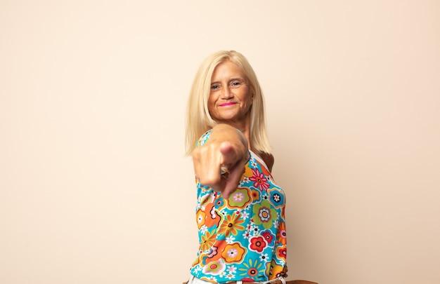 Mulher de meia-idade sorrindo com orgulho e confiança fazendo a pose número um triunfantemente, sentindo-se uma líder
