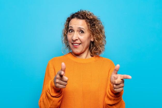 Mulher de meia-idade sorrindo com uma atitude positiva, bem-sucedida e feliz apontando