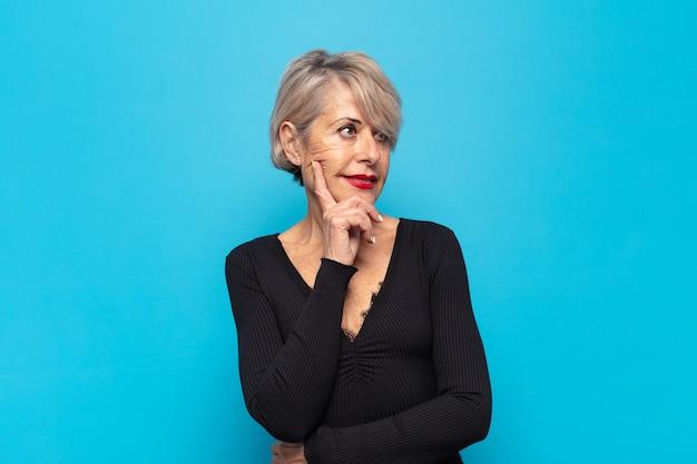 Mulher de meia-idade sorrindo com uma expressão feliz e confiante com a mão no queixo