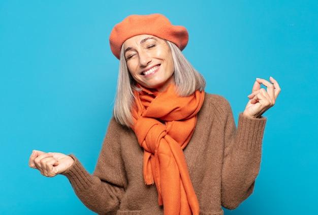 Mulher de meia idade sorrindo, despreocupada, relaxada e feliz, dançando e ouvindo música, se divertindo em uma festa