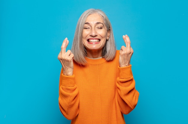 Mulher de meia idade sorrindo e cruzando os dedos ansiosamente, preocupada e desejando ou esperando por boa sorte