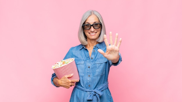 Mulher de meia-idade sorrindo e parecendo amigável, mostrando o número cinco ou quinto com a mão para a frente, conceito de filme em contagem regressiva
