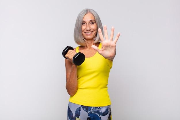Mulher de meia-idade sorrindo e parecendo amigável, mostrando o número cinco ou quinto com a mão para a frente, em contagem regressiva. conceito de fitness