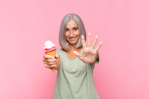Mulher de meia idade sorrindo e parecendo amigável, mostrando o número cinco ou quinto com a mão para a frente, em contagem regressiva tomando um sorvete