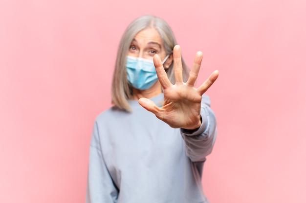 Mulher de meia-idade sorrindo e parecendo amigável, mostrando o número cinco ou quinto com a mão para a frente, em contagem regressiva