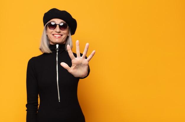 Mulher de meia idade sorrindo e parecendo amigável, mostrando o número cinco ou quinto com a mão para a frente, em contagem regressiva