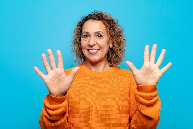 Mulher de meia-idade sorrindo e parecendo amigável, mostrando o número dez ou décimo com a mão para a frente, em contagem regressiva