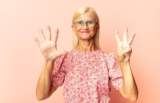 Mulher de meia idade sorrindo e parecendo amigável, mostrando o número nove ou nono com a mão para a frente, em contagem regressiva