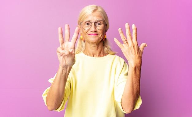 Mulher de meia-idade sorrindo e parecendo amigável, mostrando o número oito ou oitavo com a mão para a frente, em contagem regressiva