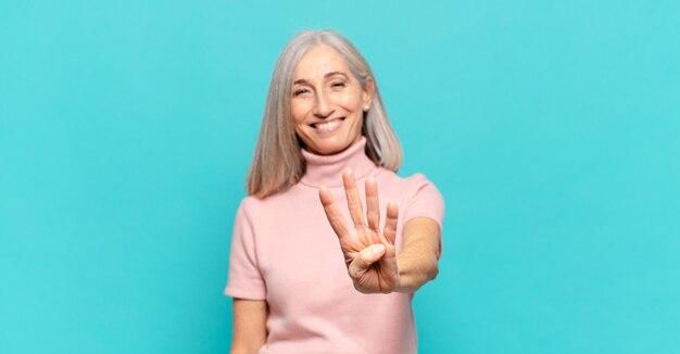 Mulher de meia idade sorrindo e parecendo amigável, mostrando o número quatro ou o quarto com a mão para a frente, em contagem regressiva