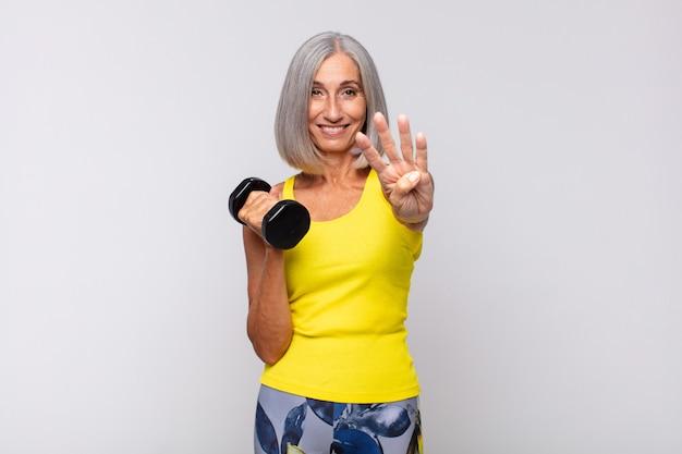 Mulher de meia idade sorrindo e parecendo amigável, mostrando o número quatro
