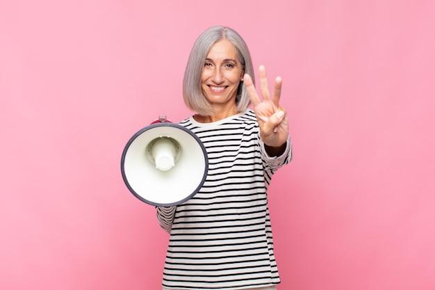 Mulher de meia-idade sorrindo e parecendo amigável, mostrando o número três ou terceiro com a mão para a frente, em contagem regressiva com um megafone