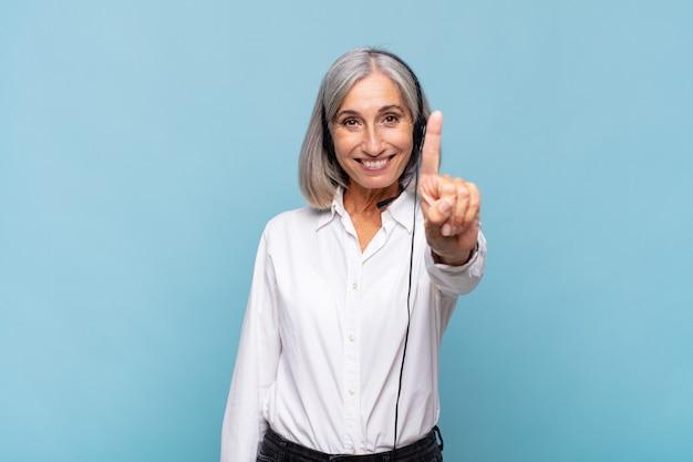 Mulher de meia-idade sorrindo e parecendo amigável, mostrando o número um ou primeiro com a mão para a frente Foto Premium