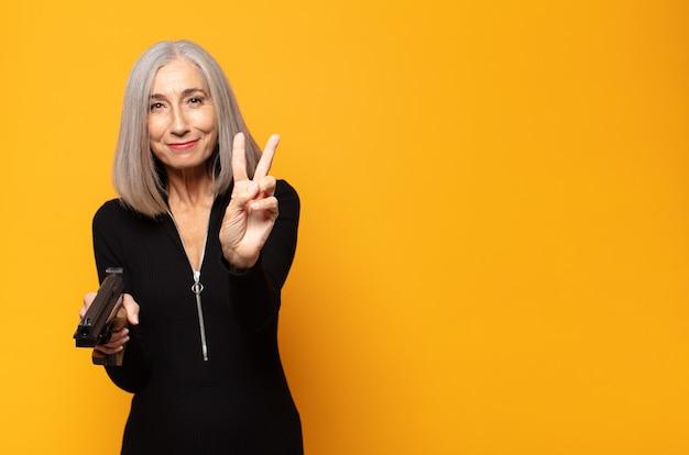 Mulher de meia-idade sorrindo e parecendo feliz, despreocupada e positiva, gesticulando vitória ou paz com uma das mãos