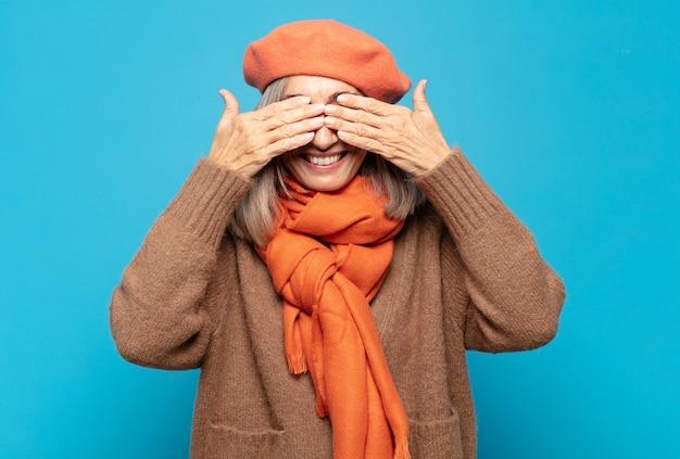 Mulher de meia-idade sorrindo e se sentindo feliz, cobrindo os olhos com as duas mãos e esperando por uma surpresa incrível