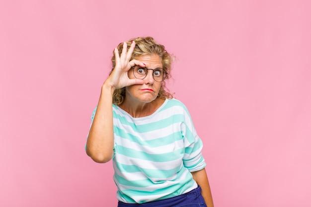Mulher de meia idade sorrindo feliz com uma careta engraçada, brincando e olhando pelo olho mágico, espionando segredos