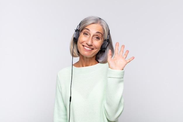 Mulher de meia idade sorrindo feliz e animada, acenando com a mão
