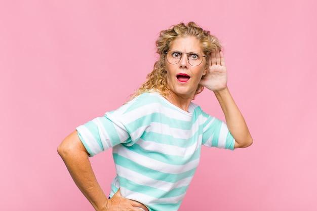 Mulher de meia-idade sorrindo, olhando curiosamente para o lado, tentando ouvir uma fofoca ou ouvindo um segredo