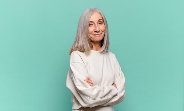 Mulher de meia-idade sorrindo para a câmera com os braços cruzados e uma expressão feliz, confiante e satisfeita, vista lateral